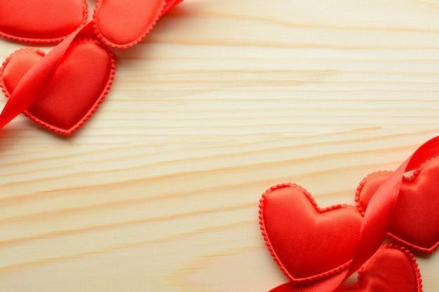 Acima, pequenos corações de tecido e fitas em fundo de madeira.