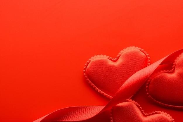 Acima, pequenos corações de tecido e fitas sobre fundo vermelho.