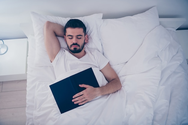 Acima, retrato de visão de alto ângulo dele, ele é simpático e atraente barbudo deitado na cama branca, dormindo pacificamente e adormecido segurando o livro à noite, tarde da noite, quarto em casa apartamento dentro de casa