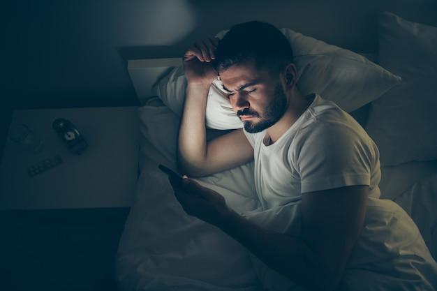 Acima, retrato de visão de alto ângulo dele, ele é um cara atraente e atraente, deitado na cama usando celular digital insônia à noite tarde da noite em casa quarto escuro iluminado casa plana dentro de casa