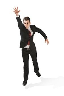 Acima, retrato frontal do empresário com cara séria. salto profissional confiante em primeiro plano da câmera. diplomata em fundo branco do estúdio. jovem caucasiano no estúdio