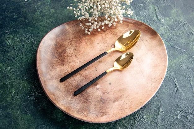 Acima, veja o prato marrom incomum com colheres douradas sobre fundo azul escuro