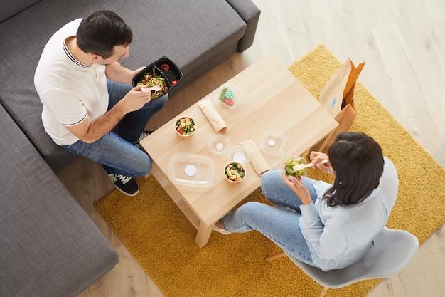 Acima, veja o retrato de um homem e uma mulher comendo um almoço para viagem no escritório ou em casa enquanto está sentado no grande sofá
