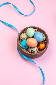 Acima, veja ovos de páscoa coloridos com ovos de codorna dentro de uma placa de madeira em uma superfície rosa claro