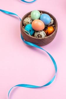 Acima, veja ovos de páscoa coloridos com ovos de codorna dentro de uma placa de madeira na superfície rosa