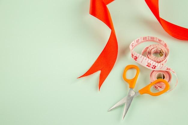 Acima ver laço vermelho com tesoura e centímetros na superfície verde alfinetes de costura costurar roupas foto de agulhas