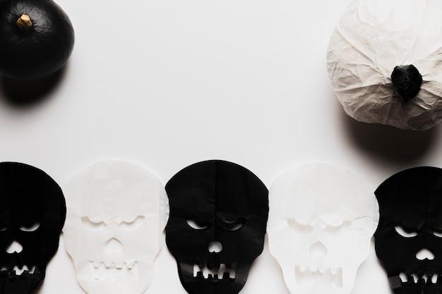 Acima vista abóboras e caveiras preto e brancas