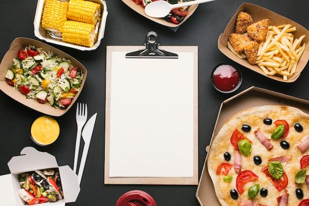 Acima vista arranjo com comida e prancheta