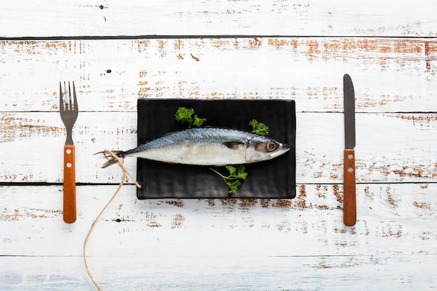 Acima vista arranjo com peixe e utensílios de mesa