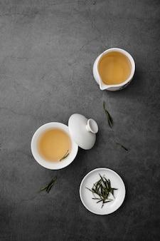 Acima vista arranjo com xícaras de chá e ervas