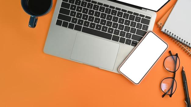 Acima vista celular, laptop, óculos, xícara de café e fundo laranja do caderno.