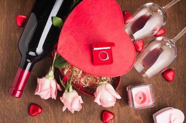 Acima vista composição com rosas e anel de noivado