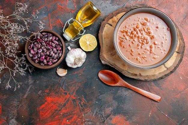 Acima, vista da clássica sopa de tomate em uma tigela azul colher na bandeja de madeira, óleo, garrafa, feijão, alho, tabela, cor mista