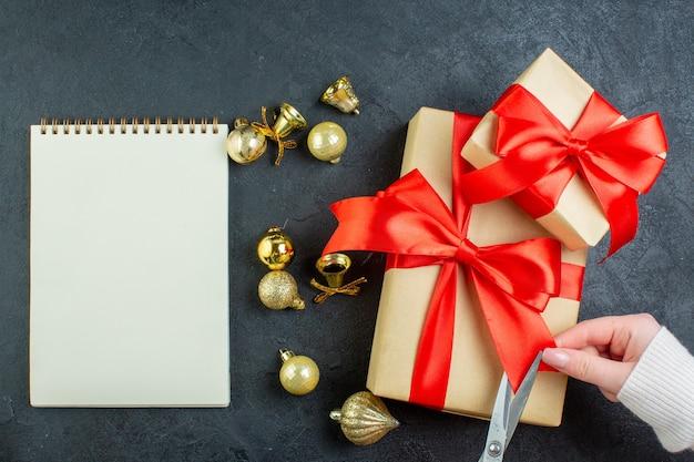 Acima, vista da mão cortando a fita vermelha na caixa de presente e acessórios de decoração ao lado do caderno espiral em fundo escuro