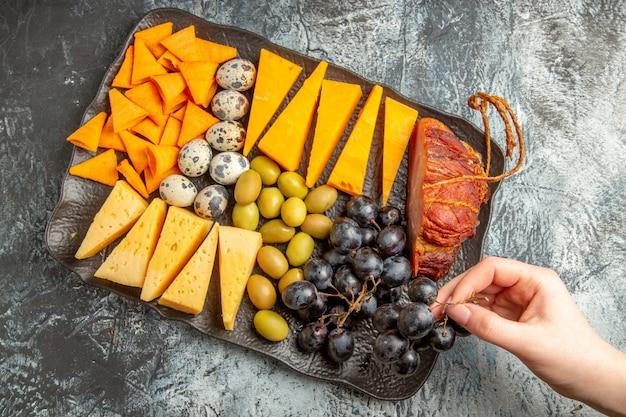 Acima, vista da mão pegando um dos alimentos do delicioso melhor lanche para vinho na bandeja marrom no fundo de gelo