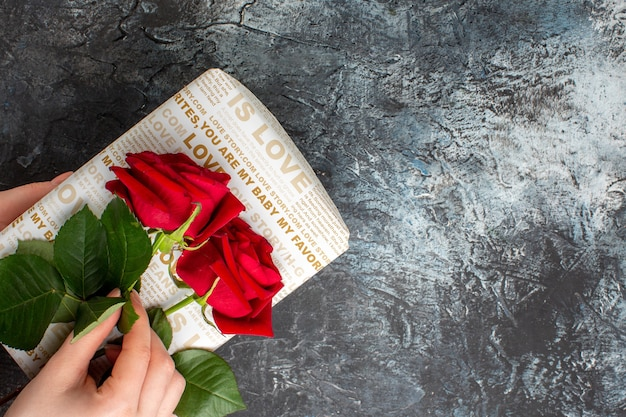 Acima, vista da mão segurando rosas vermelhas em uma linda caixa de presente em um fundo escuro gelado com espaço livre