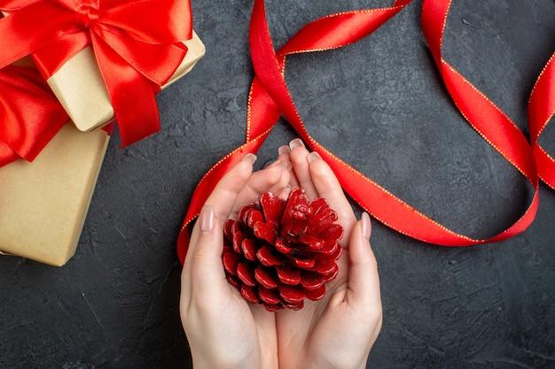 Acima, vista da mão segurando um cone de conífera e um lindo presente em fundo escuro