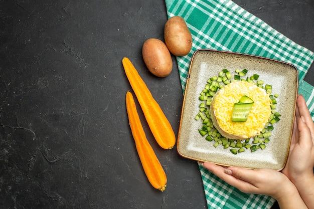 Acima, vista da mão segurando uma deliciosa salada servida com pepino picado em uma toalha verde despojada pela metade e batatas com cenoura em fundo escuro