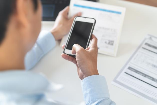Acima vista da pessoa que paga contas via aplicativo bancário do telefone móvel.