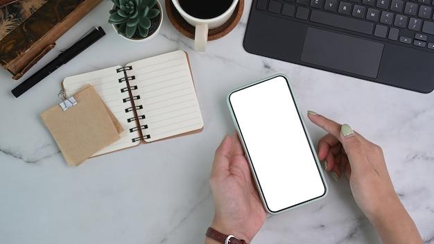 Acima vista das mãos da mulher segurando um telefone inteligente simulado com tela branca sobre fundo de mármore.