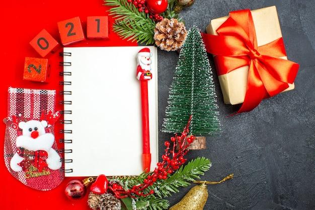 Acima, vista de acessórios de decoração de caderno espiral ramos de abeto xsmas números de meias em um guardanapo vermelho e árvore de natal de presente em fundo escuro