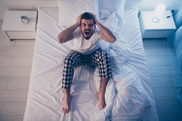 Acima, vista de alto ângulo dele, ele agradável atraente deprimido ansioso cara devastado sentado na cama sofrendo de insônia à noite tarde da noite em casa quarto iluminado casa plana