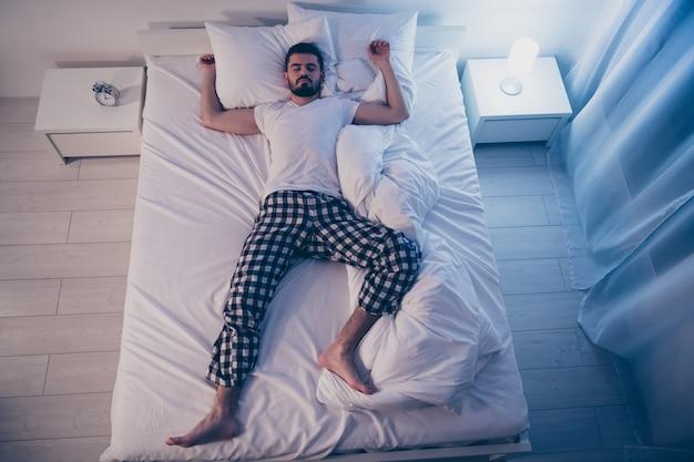 Acima, vista de alto ângulo dele, ele é agradável, atraente, sonolento, sonolento, deitado na cama, adormecido, boa vida, estilo de vida à noite tarde da noite em casa quarto iluminado