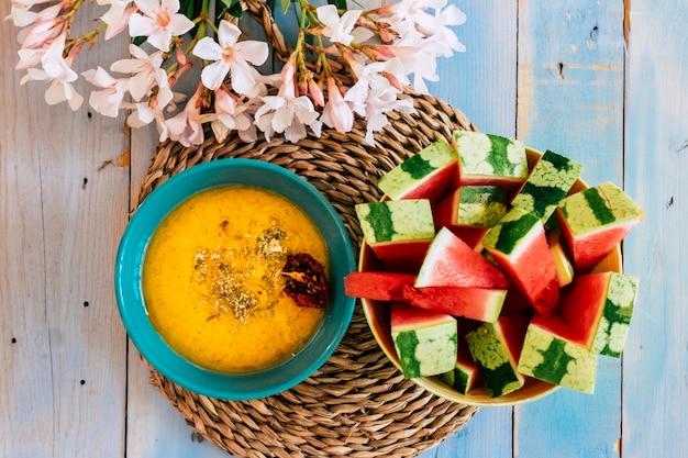 Acima, vista de comida colorida com sopa de vegetais amarelos e melancia vermelha fresca em uma mesa amarela azul com decoração de flores