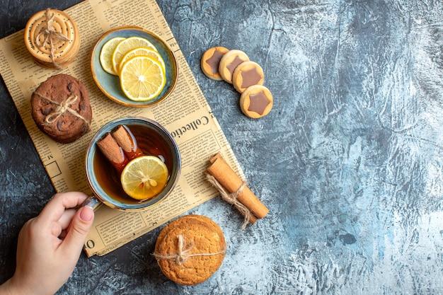 Acima, vista de deliciosos biscoitos e uma mão segurando uma xícara de chá preto com canela em um jornal velho