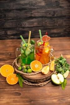 Acima, vista de deliciosos sucos frescos e frutas em uma bandeja de madeira em um fundo marrom