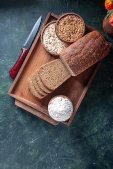 Acima, vista de fatias de pão preto na bandeja de madeira marrom farinha de aveia e trigo sarraceno no fundo azul
