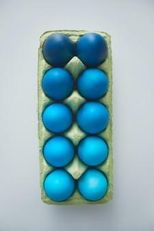 Acima, vista de lindos ovos de páscoa azuis na caixa, dispostos em uma composição mínima no fundo branco, copie o espaço