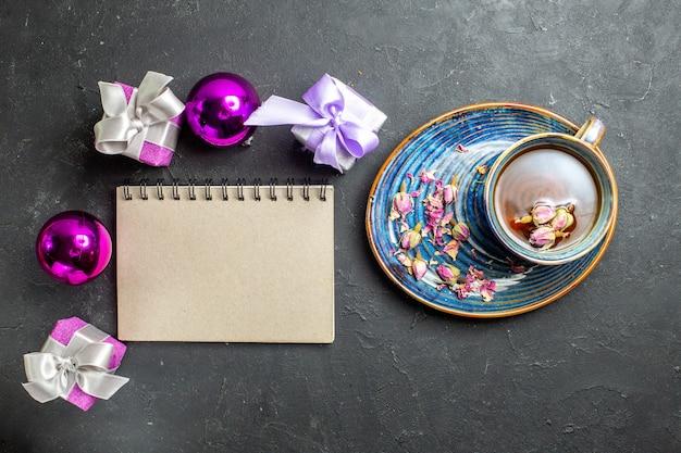 Acima, vista de presentes coloridos e acessórios de decoração, uma xícara de chá preto ao lado do caderno em fundo escuro