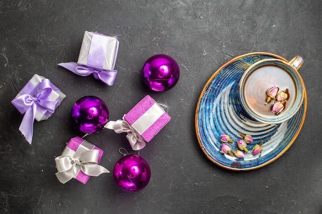 Acima, vista de presentes coloridos e acessórios de decoração, uma xícara de chá preto em fundo escuro