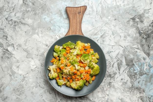 Acima, vista de salada de legumes fresca e saudável em uma tábua de madeira na mesa branca