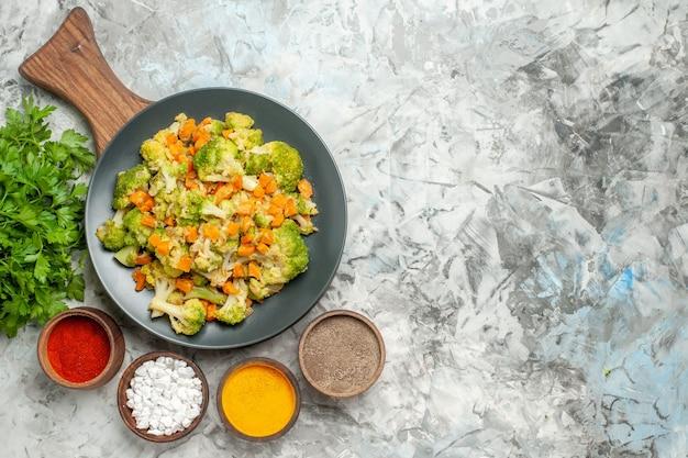 Acima, vista de salada de vegetais saudáveis, diferentes especiarias e brócolis na mesa branca
