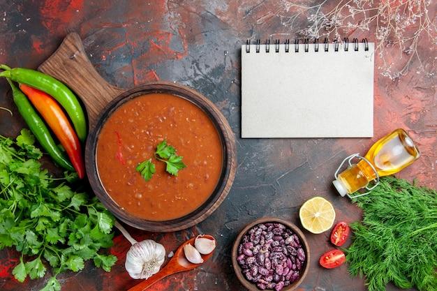 Acima, vista de sopa de tomate caída de grãos de garrafa de óleo na tábua e caderno em uma mesa de cores misturadas
