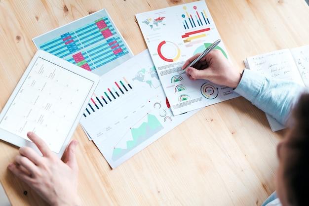 Acima, vista de um analista irreconhecível sentado à mesa e visualizando dados e documentos online enquanto faz previsões de negócios