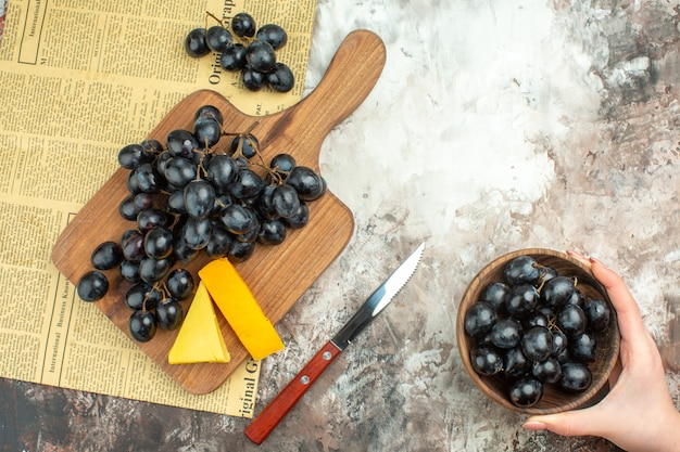Acima, vista de um delicioso cacho de uva preta e vários tipos de queijo na tábua de madeira