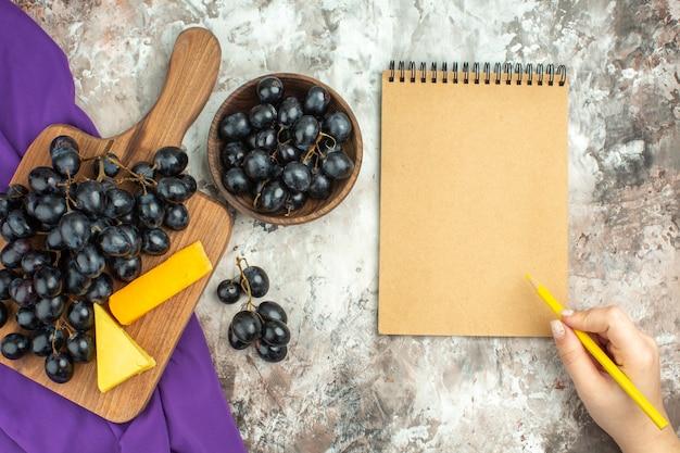 Acima, vista de um delicioso cacho de uva preta fresco e queijo na tábua de madeira