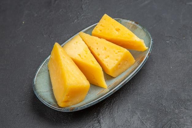 Acima, vista de um delicioso queijo fatiado amarelo em uma placa azul sobre fundo preto