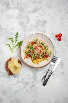 Acima, vista de uma deliciosa salada de frango com vegetais, tomate e abacaxi seco, talheres em uma superfície branca manchada com espaço livre