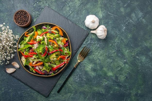 Acima, vista de uma deliciosa salada de vegetais com vários ingredientes em uma tábua de corte preta