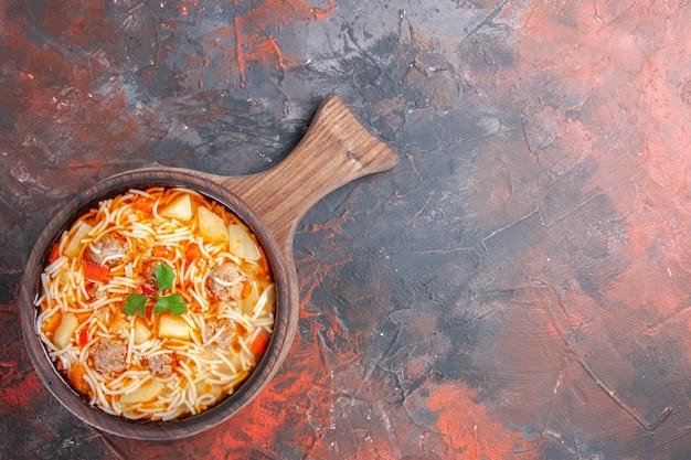 Acima, vista de uma deliciosa sopa de macarrão com frango em uma tábua de madeira em fundo escuro