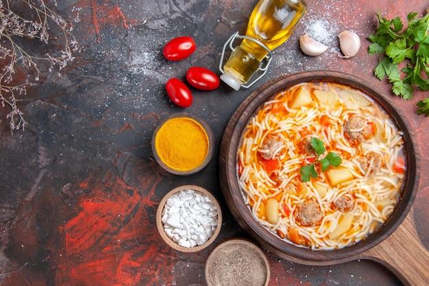 Acima, vista de uma deliciosa sopa de macarrão com frango na tábua de madeira, óleo de garrafa de especiarias diferentes e verdes na mesa escura