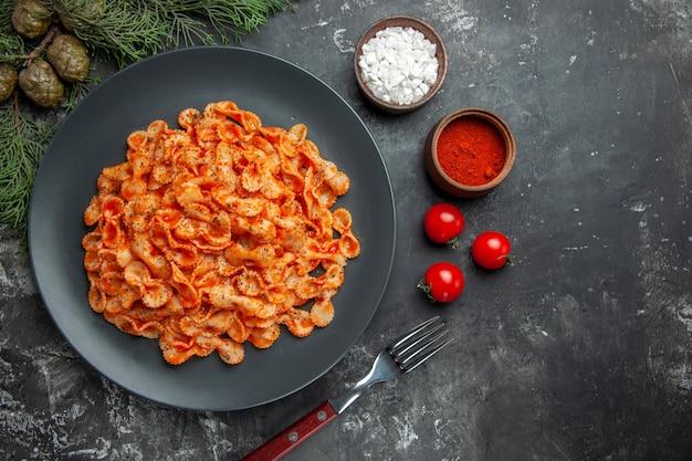 Acima, vista de uma refeição de massa fácil para o jantar em um prato preto e um garfo em diferentes especiarias e tomates em um fundo escuro