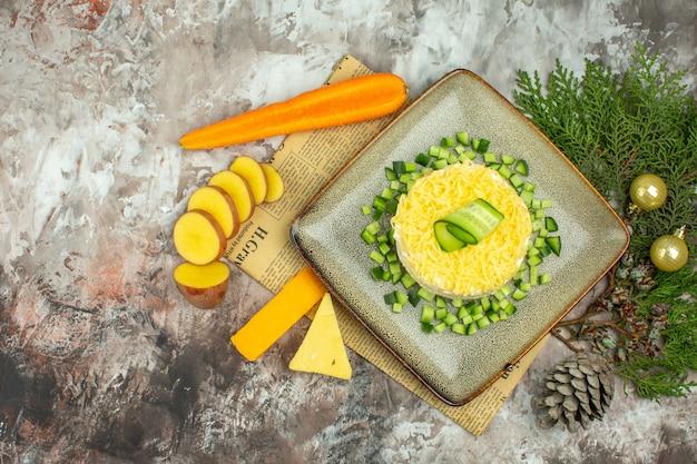 Acima, vista de uma saborosa salada em um jornal velho e dois tipos de queijo e cenoura, batatas picadas, acessórios de ano novo na mesa de cores misturadas