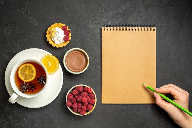 Acima, vista do caderno e saboroso jantar com panquecas deliciosas frescas em um prato branco e uma xícara de chá preto de chocolate e mel de framboesa em fundo escuro