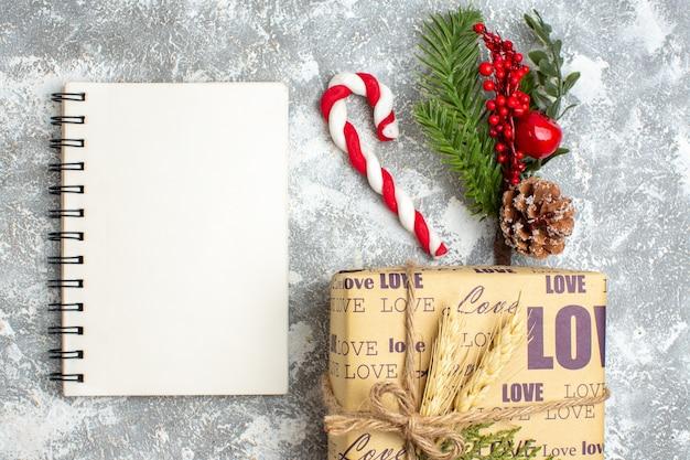 Acima, vista do caderno fechado e lindo presente de natal embalado com inscrição de amor pequenos cupcakes cand fir branches acessórios de decoração cone de conífera na superfície do gelo