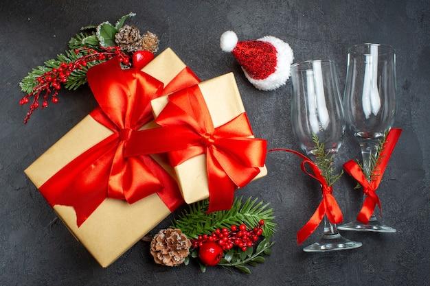 Acima, vista do clima de natal com belos presentes com fita em forma de arco e acessórios de decoração de ramos de abeto chapéu de papai noel taças de vidro cones de coníferas em um fundo escuro